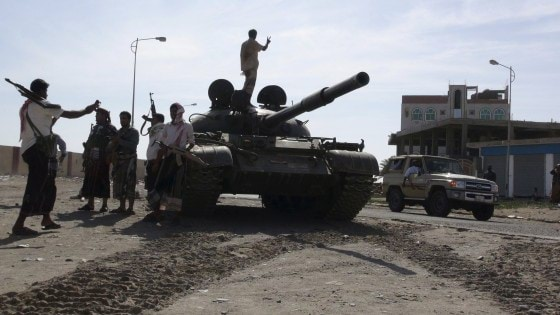 Militia men loyal to Yemen's President Abd-Rabbu Mansour Hadi take photos near an army tank in Yemen's southern port city of Aden