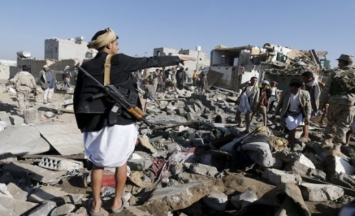 An armed man gestures as he stands on the rubble of houses destroyed by an air strike near Sanaa Airport