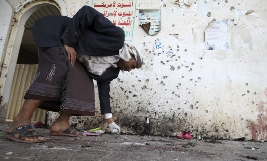 A crime scene investigator looks at the ground after a suicide bomb attack at a mosque in Sanaa