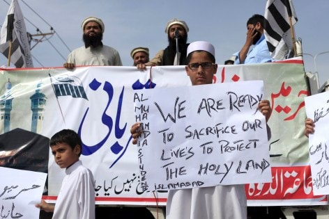 A supporter of the Jamaat-ud-Dawa Islamic organization holds a placard during a demonstration in support of Saudi Arabia over its intervention in Yemen, in Islamabad