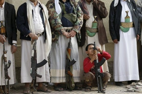 Boy holds his father's rifle as they attend a protest by followers of the Houthi movement against the Saudi-led air strikes in Sanaa