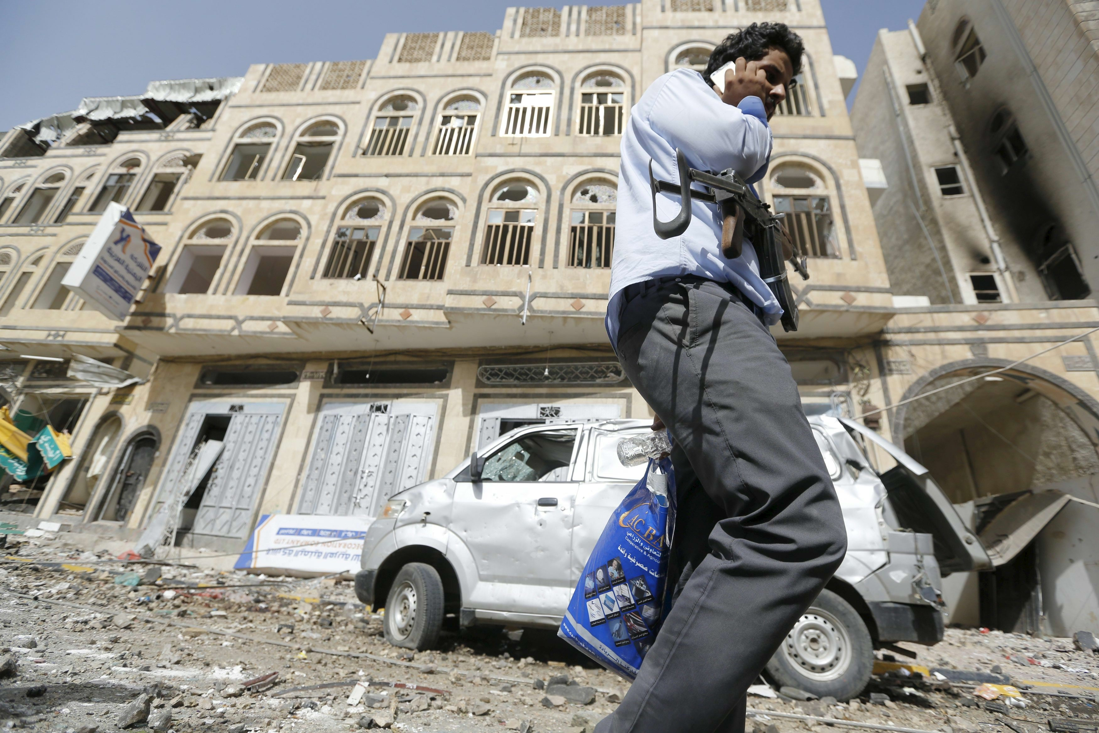 A man carrying a weapon talks on his mobile phone near a building damaged by an air strike on a nearby Scud missile base in Yemen's capital Sanaa