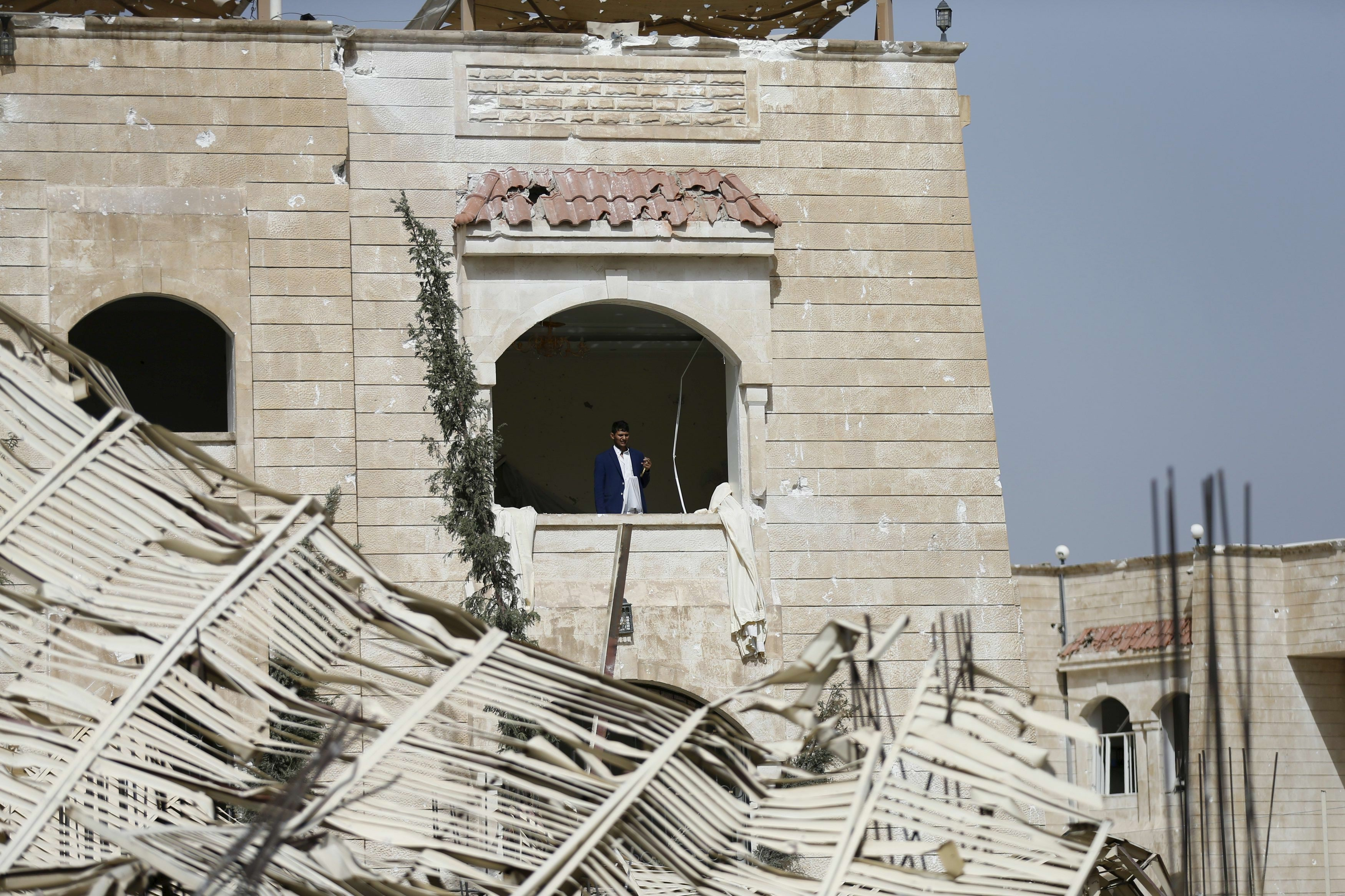A man looks out from his house damaged by an air strike on a nearby Scud missile base in Yemen's capital Sanaa