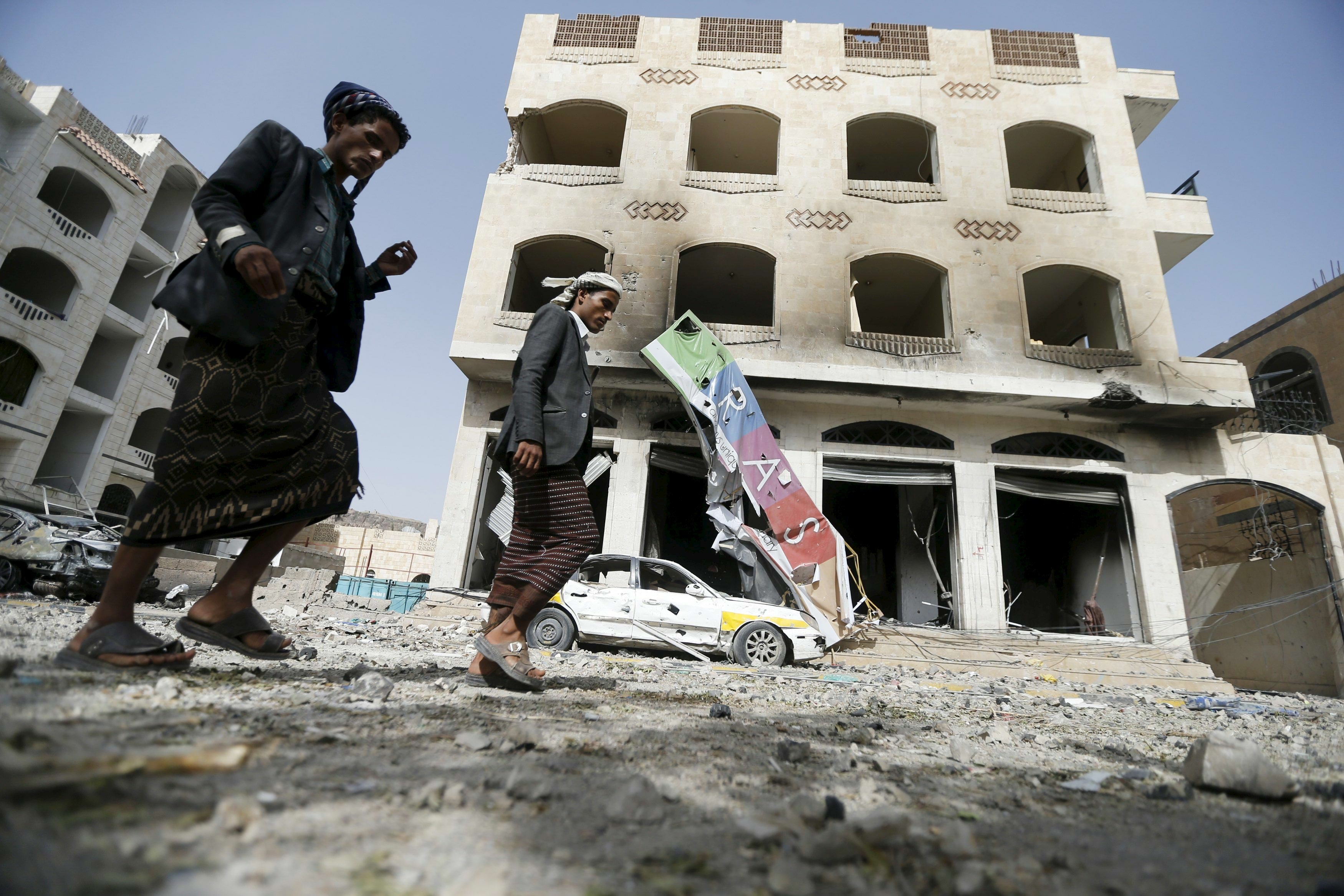 People walk by a building damaged by an air strike on a nearby Scud missile base in Yemen's capital Sanaa