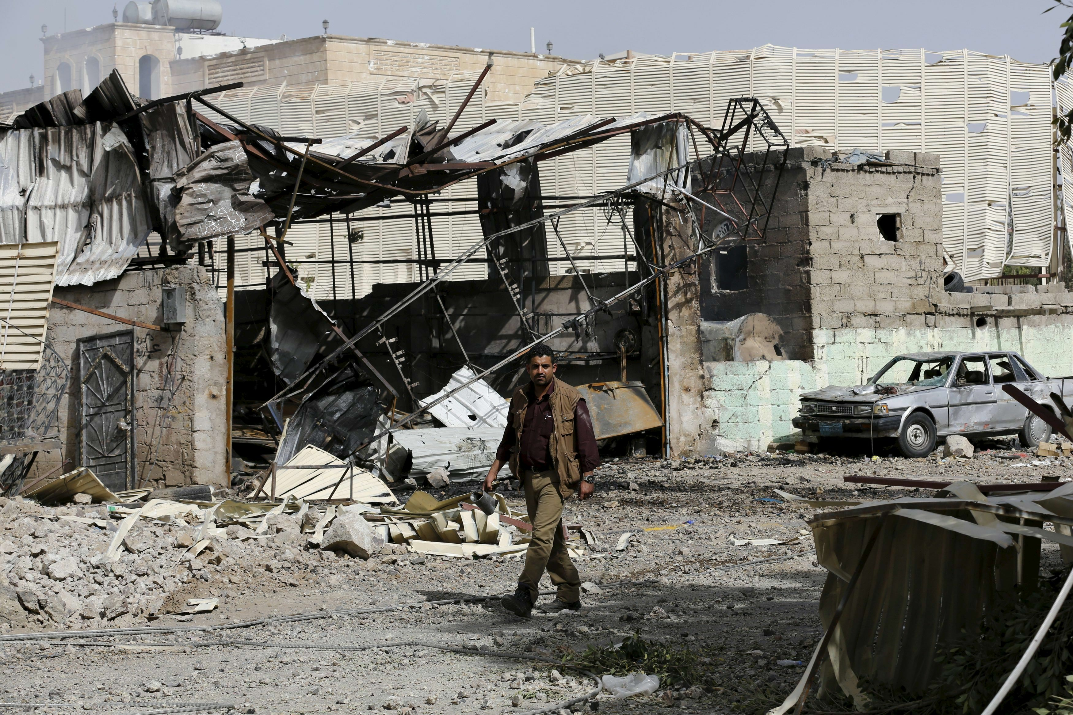 A man walks by a workshop damaged by an air strike on a nearby Scud missile base in Yemen's capital Sanaa