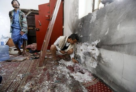 People inspect damage caused by a bomb explosion at a mosque in Yemen's capital Sanaa