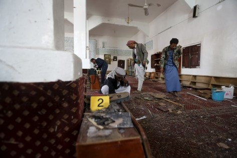 People look for evidence at the site of a bomb explosion at a mosque in Yemen's capital Sanaa