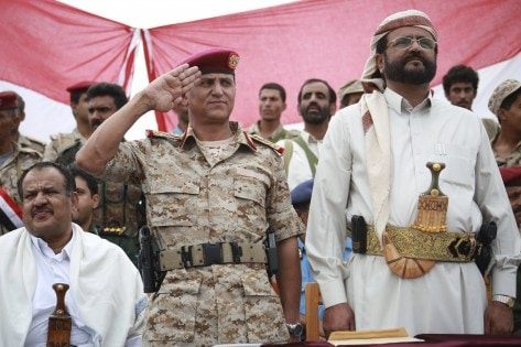 Commander of the 3rd Region of Yemen's army, General Abdul-Rab al-Shaddadi, salutes as he and the governor of the northern province of Marib, Sultan al-Erada watch a parade for forces loyal to the country's President Abd-Rabbu Mansour Hadi in Marib