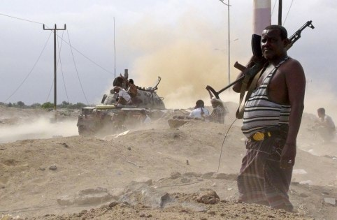 Anti-Houthi fighter of the Southern Popular Resistance stands guard as comrades fire from a tank in Yemen's southern port city of Aden