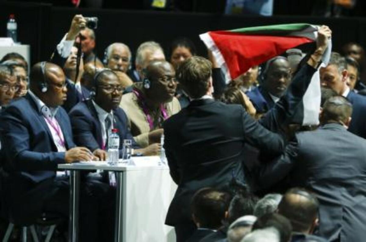 Security officers block a pro-Palestine protestor at the 65th FIFA Congress in Zurich