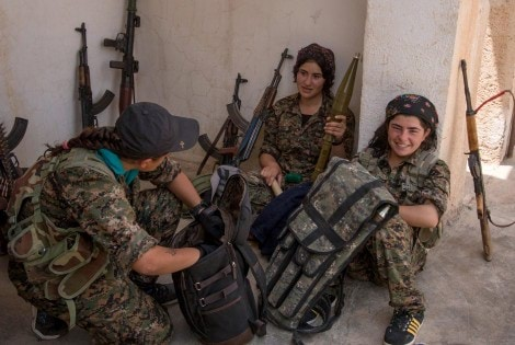 Armed Kurdish female fighters from People's Protection Units (YPG) talk to each other in the Assyrian village of Tel Nasri