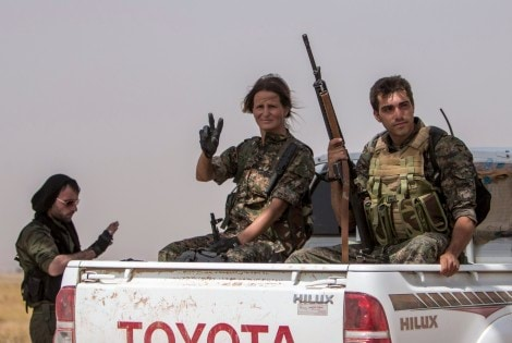 Foreign fighters loyal to the Kurdish People's Protection Units (YPG) pose as they sit with weapons on a pickup truck in Tel Tamr town