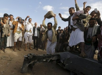 People destroy part of a Saudi fighter jet found in Bani Harith district north of Yemen's capital Sanaa