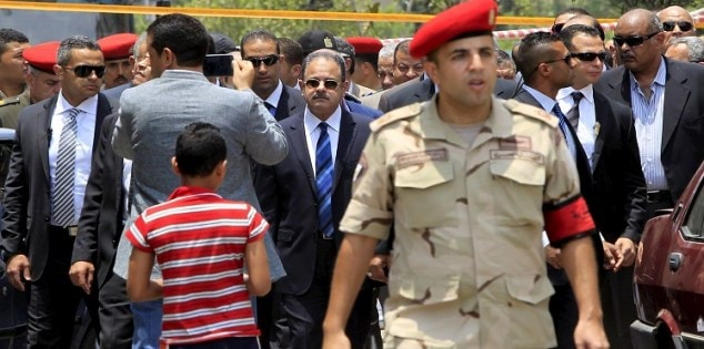 Egyptian Interior Minister Magdy Abdel Ghaffar investigates the site of a car bomb attack on the convoy of Egyptian public prosecutor Hisham Barakat near his house at Heliopolis district in Cairo