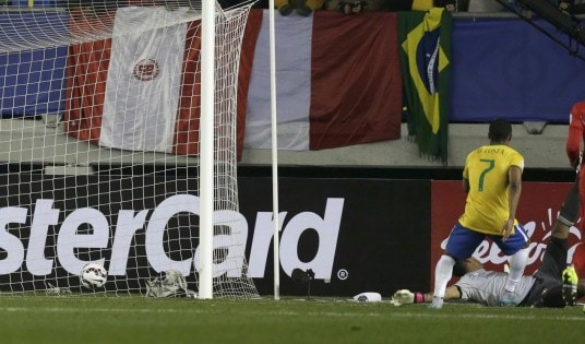 Brazil's Douglas scores a goal on Peru's goalie Gallese during their first round Copa America 2015 soccer match at Estadio Municipal Bicentenario German Becker in Temuco
