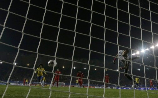 Peru's goalie Gallese allows in a goal by Brazil's Douglas during their first round Copa America 2015 soccer match at Estadio Municipal Bicentenario German Becker in Temuco