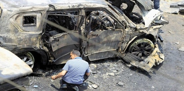A crime scene investigator investigates the site of a car bomb attack on the convoy of Egyptian public prosecutor Hisham Barakat near his house at Heliopolis district in Cairo