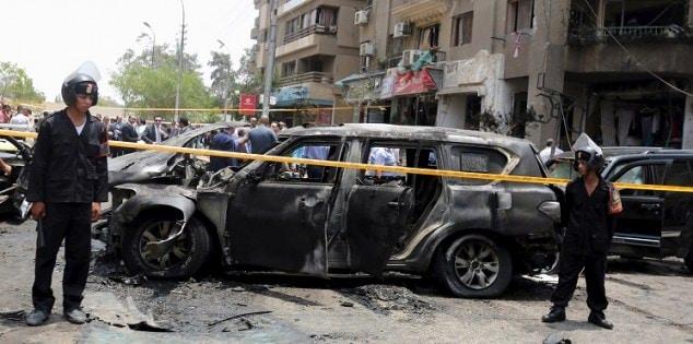 Policemen secure the site of a car bomb attack on the convoy of Egyptian public prosecutor Hisham Barakat near his house at Heliopolis district in Cairo