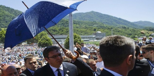 A stone is thrown at Serbia's Prime Minister Vucic as bodyguards use umbrella to protect him during unrest at a ceremony marking the 20th anniversary of the Srebrenica massacre in Potocari