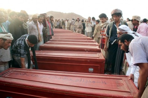 Relatives gather around coffins of Yemeni troops killed by Saudi-led air strikes on an army base that was hit in error, in al-Abr on the border with Saudi Arabia