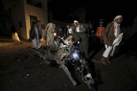 Police officers and Houthi militants inspect the site of a car bomb attack in Yemen's capital Sanaa