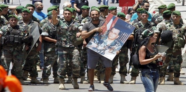 A man carries a picture of Lebanese opposition Christian leader and head of the Free Patriotic Movement Michel Aoun near Lebanese army members during a protest in Beirut, Lebanon