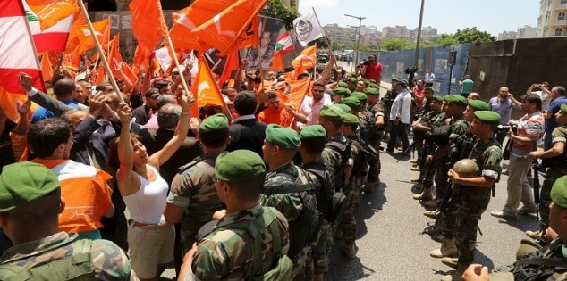 Supporters of the Free Patriotic Movement wave their parties flags near Lebanese army members during a protest in Beirut, Lebanon