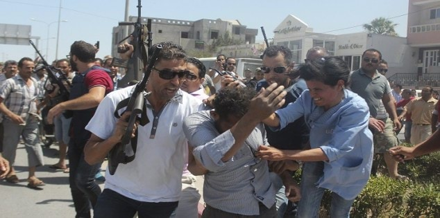 Police officers control the crowd while surrounding a man suspected to be involved in opening fire on a beachside hotel in Sousse