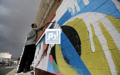 Pro-Houthi activist paints graffiti during a campaign against Saudi-led air strikes on the wall of the Saudi embassy in Sanaa