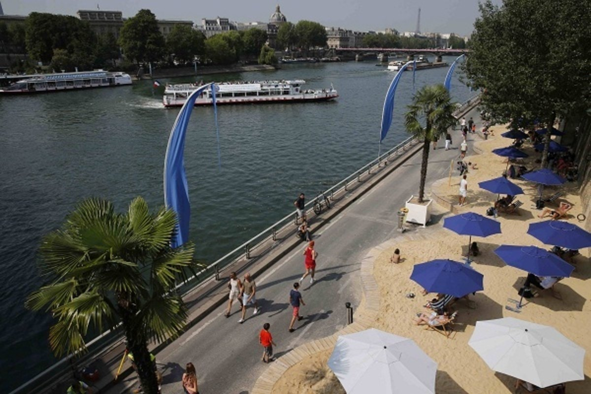 "People sunbathe on the banks of the river Seine during "" Paris plage "" event  in Paris"