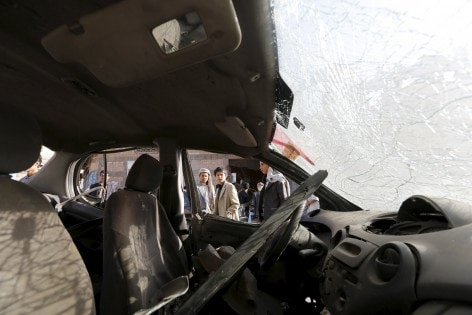 People are pictured through the window of a damaged car outside a mosque hit by two bombings in Yemen's capital Sanaa