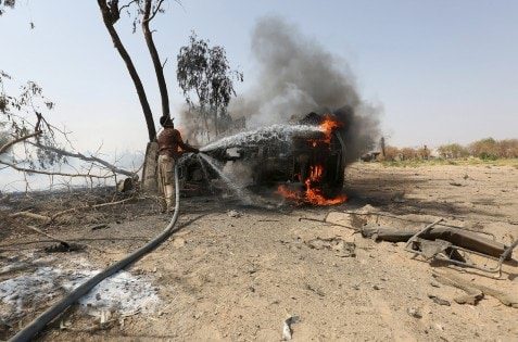 Militiaman loyal to Yemen's government extiguishes the fire on a car destroyed in a landmine explosion in Yemen's central province of Marib