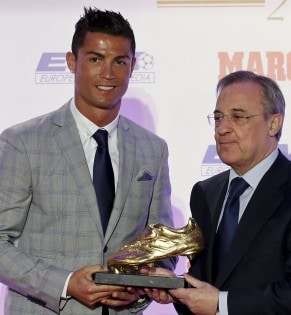Real Madrid's striker Cristiano Ronaldo receives his fourth Golden Boot trophy from Real Madrid's president Florentino Perez during a ceremony in Madrid, Spain