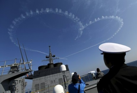 "Member of JMSDF looks at a performance by JASDF aerobatic flight team ""Blue Impulse"" during JMSDF's fleet review at Sagami Bay, off Yokosuka"