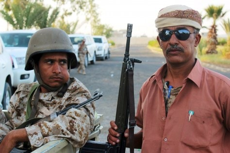 Yemeni soldier chews qat next to a tribal resistance fighter in Marib, Yemen