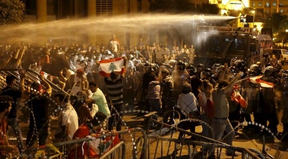 Lebanese protesters are sprayed with water during a protest in Martyr square, Downtown Beirut, Lebanon