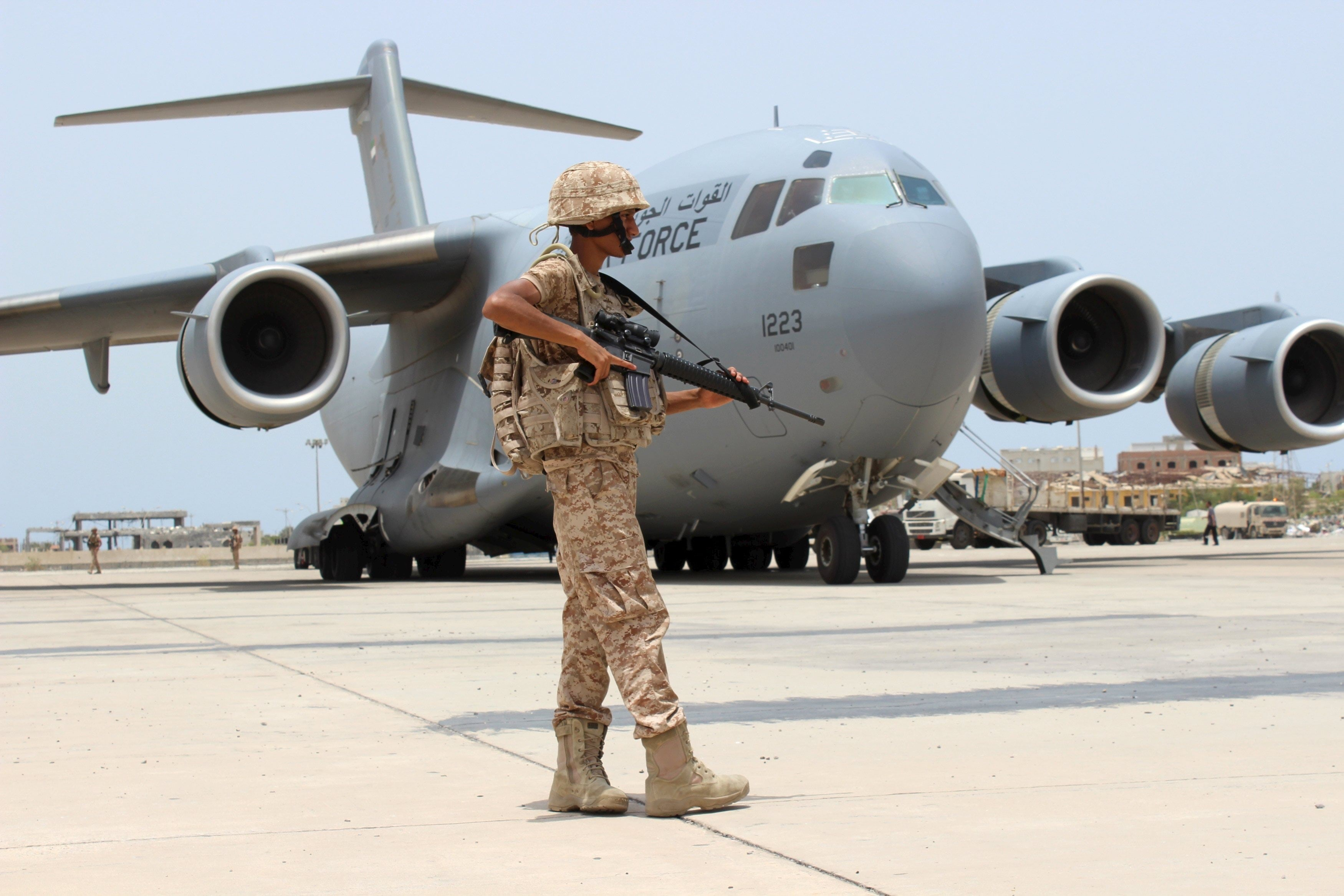 Soldier from the United Arab Emirates stands guard next to a UAE military plane at the airport of Yemen's southern port city of Aden