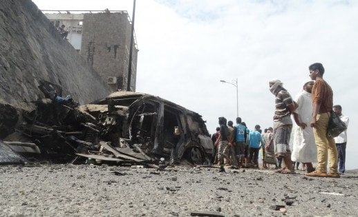 People gather at the site of a car bomb attack that killed the governor of Yemen's southern port city of Aden