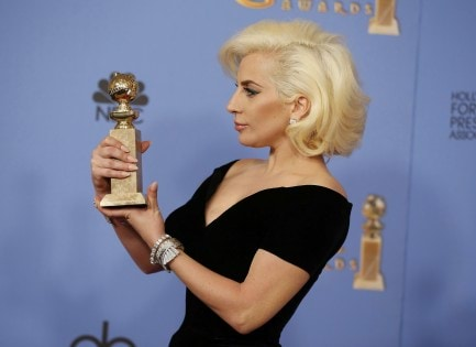 Lady Gaga poses with her award during the 73rd Golden Globe Awards in Beverly Hills