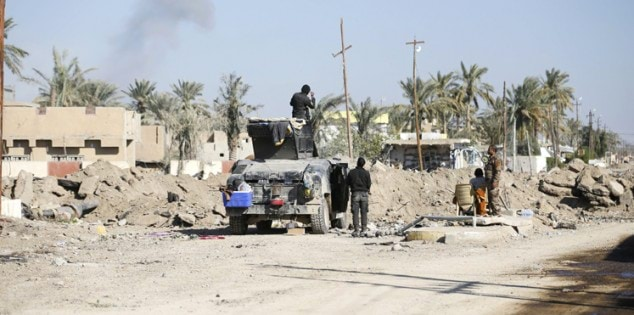 Iraqi security forces gather during a patrol in the city of Ramadi