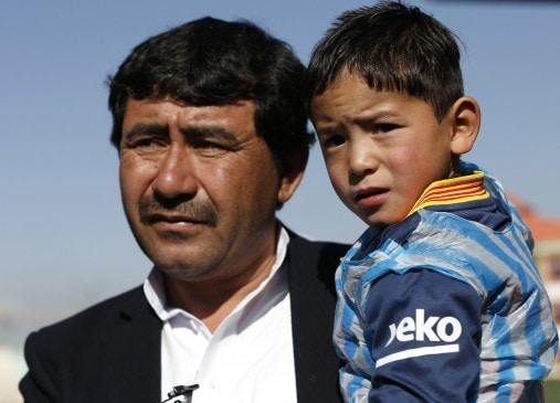 Five year-old Murtaza Ahmadi wears a shirt of Barcelona's star Lionel Messi as his father talks to the media at the Afghan Football Federation headquarters in Kabul