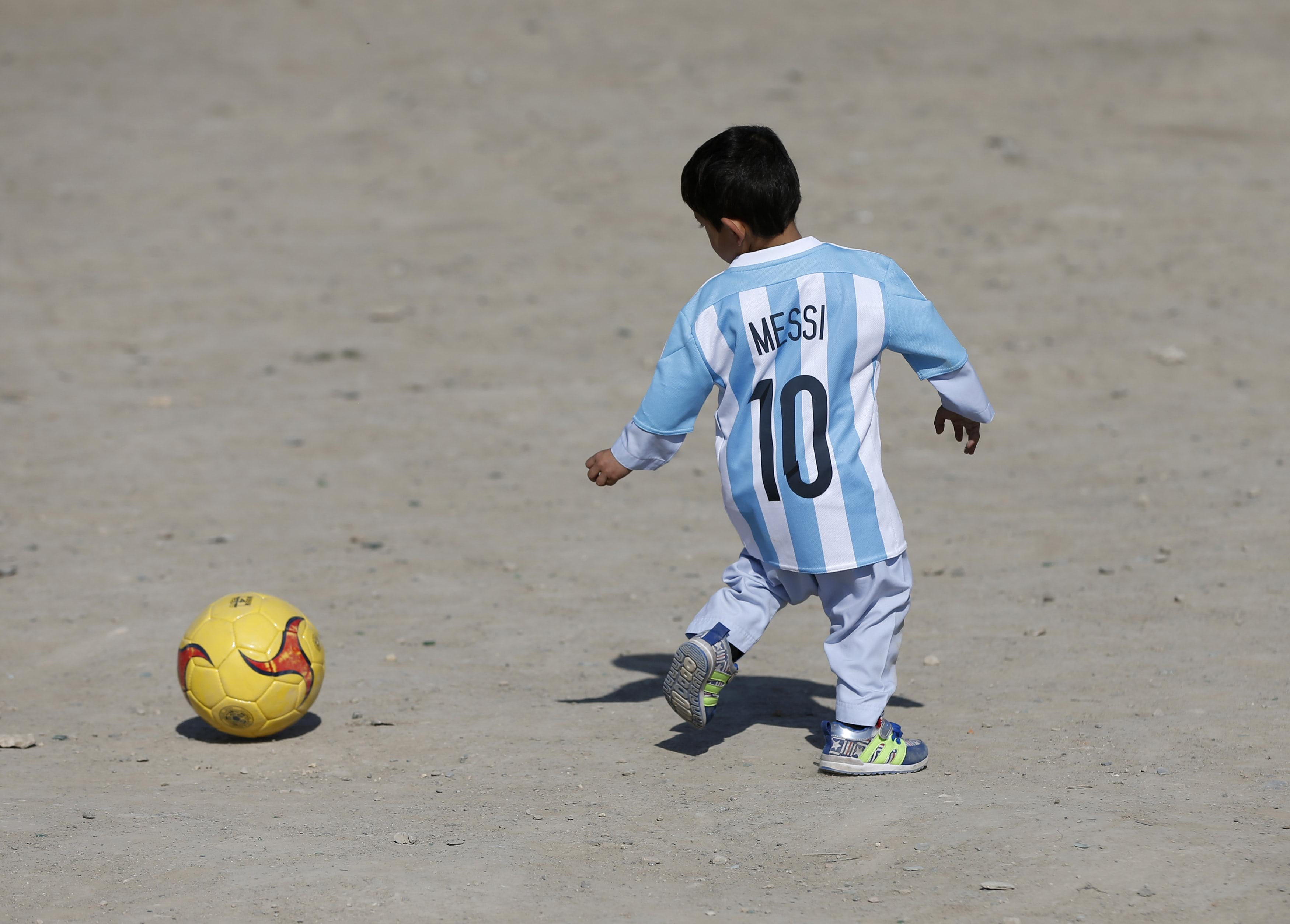 Five year-old Ahmadi, an Afghan Messi fan, wears a shirt signed by Barcelona star Messi, as he plays football at the open area in Kabul