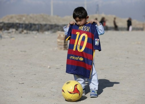 Five year-old Ahmadi, an Afghan Messi fan, shows a shirt signed by Barcelona star Messi, before he plays football at the open area in Kabul