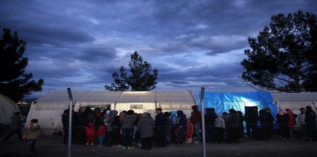 Temporarily stranded Syrian and Iraqi refugees line up o receive aid at a camp by the Greek-Macedonian border near the Greek village of Idomeni
