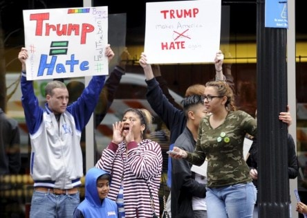 Protesters yell across the street at supporters of U.S. Republican presidential candidate Trump waiting in line for a campaign rally in Kansas City