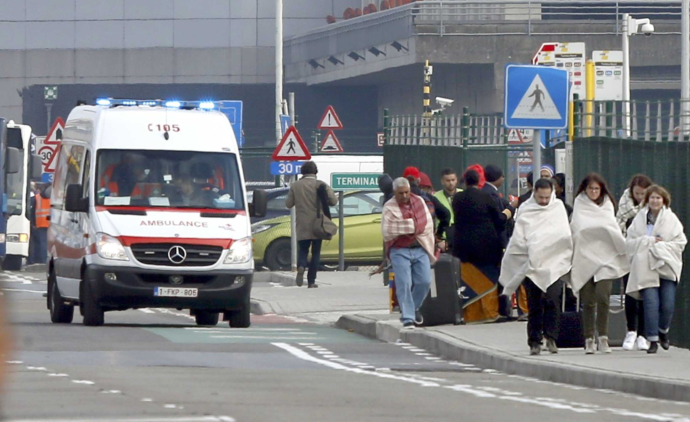 People wrapped in blankets leave the scene of explosions at  Zaventem airport near Brussels, Belgium