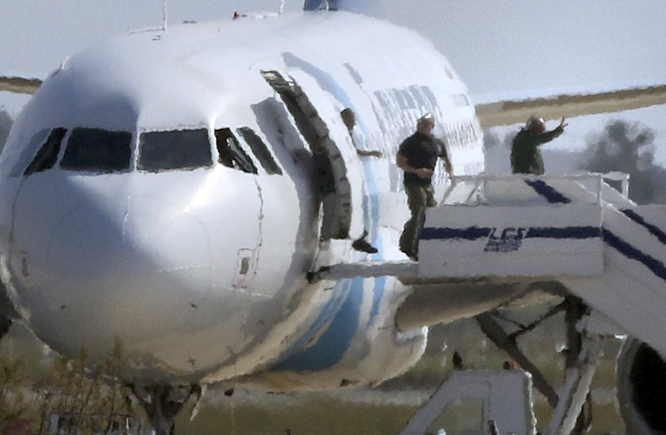 Unidentified people leave the hijacked Egyptair Airbus A320 at Larnaca Airport in Larnaca, Cyprus