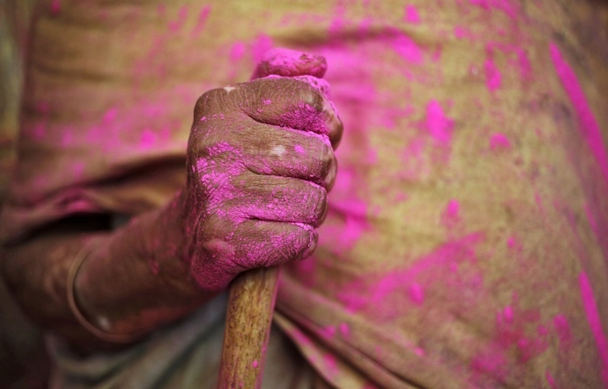 A widow daubed in colours holds a stick as she takes part in the Holi celebrations organised by non-governmental organisation Sulabh International at a temple at Vrindavan