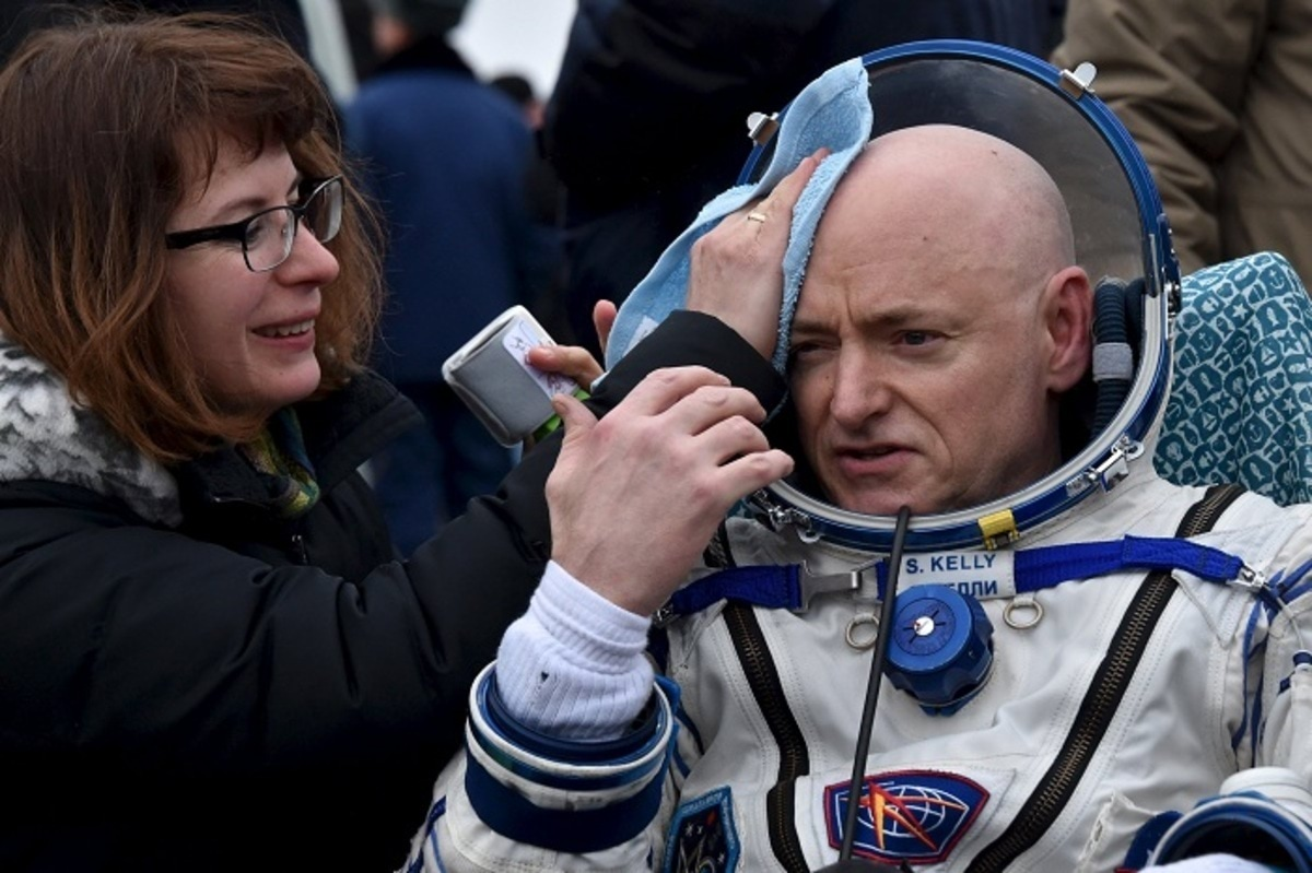 U.S. astronaut Kelly is assisted by ground personnel shortly after landing near Dzhezkazgan
