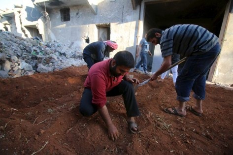 Residents grow their own vegetables near the rubble of damaged buildings in the rebel held area of al-Jazmati neighbourhood of Aleppo